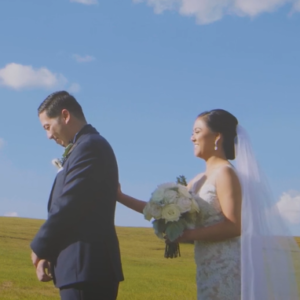 Bride standing behind her husband with her right hand on his back.